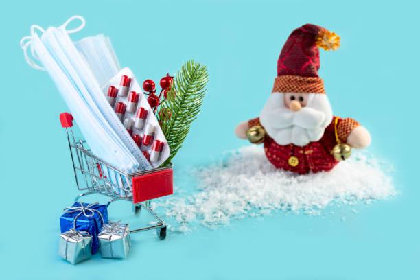 Christmas medical card with masks, pills, Christmas gifts and Santa. stock photo