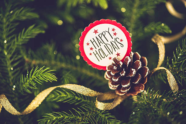 christmas message with pinecone on real christmas tree. happy holidays - happy holidays stock pictures, royalty-free photos & images