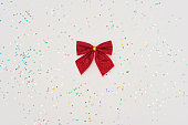 istock Christmas minimal composition. Red bow isolated on white background with glitter. New Year concept. Copy space. 1265633861