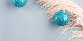 Christmas minimal festive gray background with pampas grass and blue sparkling disco bauble. New year backdrop banner