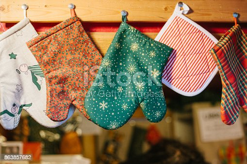 839034546 istock photo Christmas mittens potholders hang in kitchen against the background of blurry kitchen appliances. 863857682