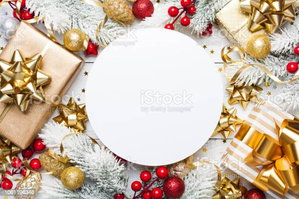 Photo of Christmas mockup with gift or present boxes, snowy fir tree and holiday decorations on white wooden table top view.