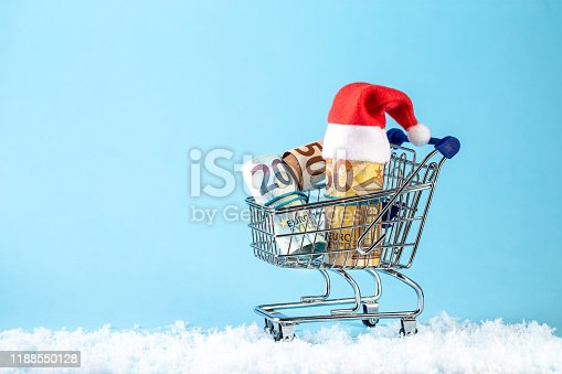 Christmas money gift with Santa Claus hat on pastel blue background. Happy New Year greeting card. The concept of Christmas shopping. Copy space for the text