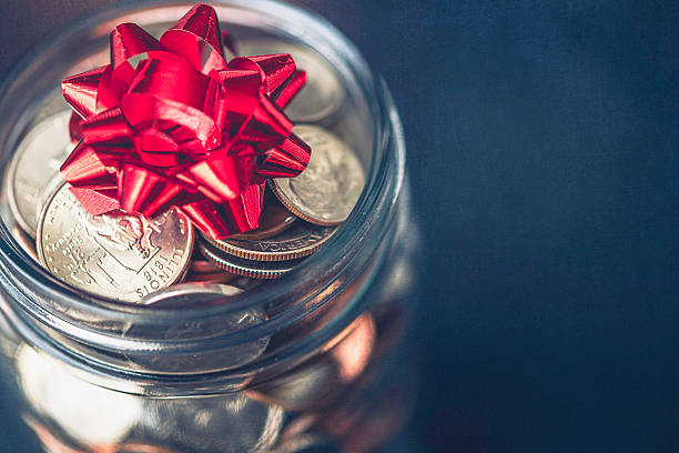 Christmas money jar with American currency and topped with bow stock photo