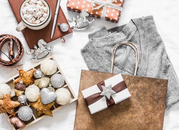 Weihnachtsstimmung Hintergrund. Festliches Weihnachtseinkaufskonzept. Grau Kaschmir Pullover, Geschenk-Box, Notizblock, Weihnachtsdekorationen, heiße Schokolade mit Marshmallow auf weißem Hintergrund, Top-Ansicht. Flache Verlegung – Foto