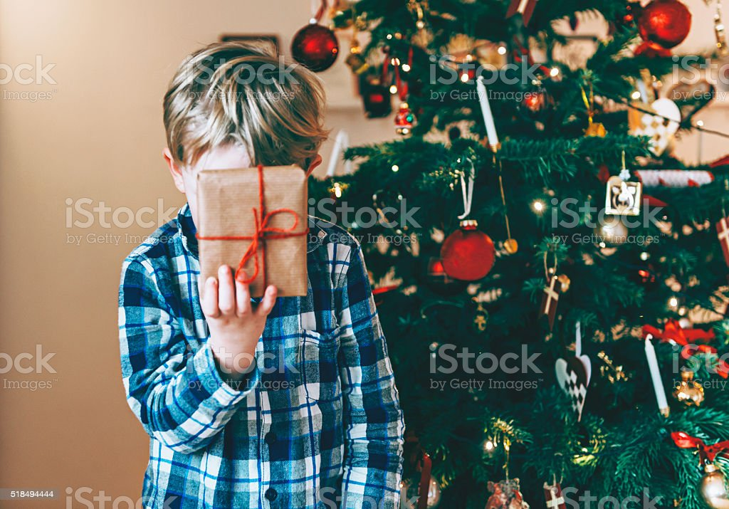Christmas morning and boy in pajamas holds a present stock photo