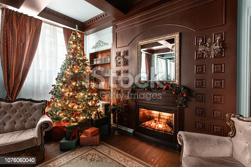 istock Christmas morning. Gifts at the Christmas tree. Classic apartments with a fireplace. Room with shelves of books 1076060040