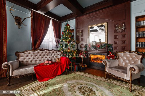 istock Christmas morning. Gifts at the Christmas tree. Classic apartments with a fireplace. 1076189956