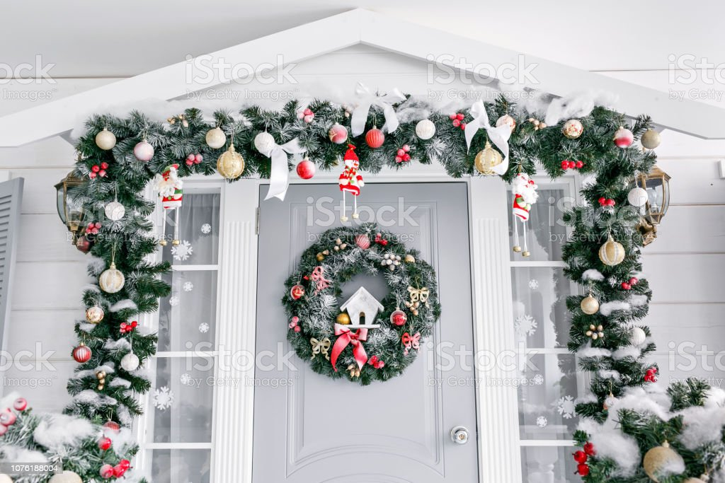 Christmas morning. porch a small house with a decorated door with a...