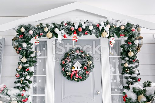 Christmas morning. porch a small house with a decorated door with a Christmas wreath. Winter fairy tale