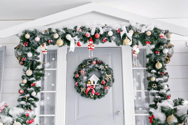christmas morning. house entrance decorated for holidays. christmas decoration. garland of fir tree branches and lights on the railing - balão enfeite imagens e fotografias de stock