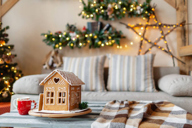 Christmas morning in the bright living room. Homemade gingerbread house on background room decorated for Christmas. stock photo