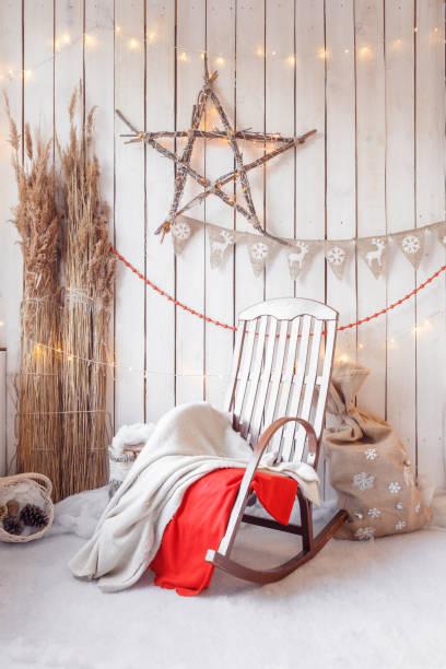weihnachtsmorgen. schaukelstuhl mit dekorationen von brennholz und holzwand - veranda decke stock-fotos und bilder