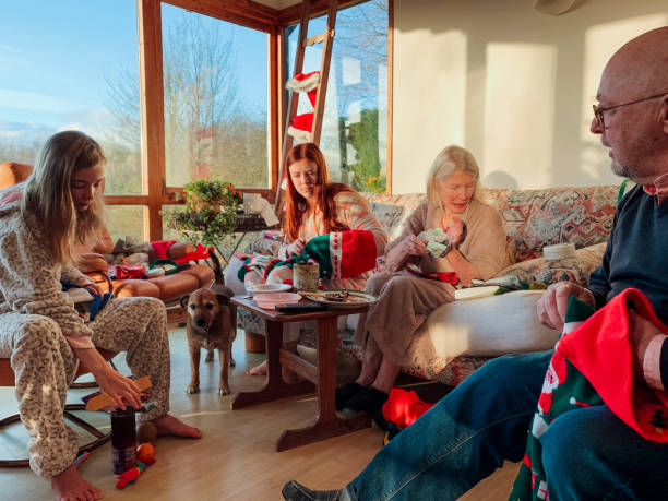 Christmas Morning Traditions A multi-generation family including two sisters, a father and grandmother are sitting in their living room on Christmas morning, opening presents and checking their stockings. 12 17 months stock pictures, royalty-free photos & images