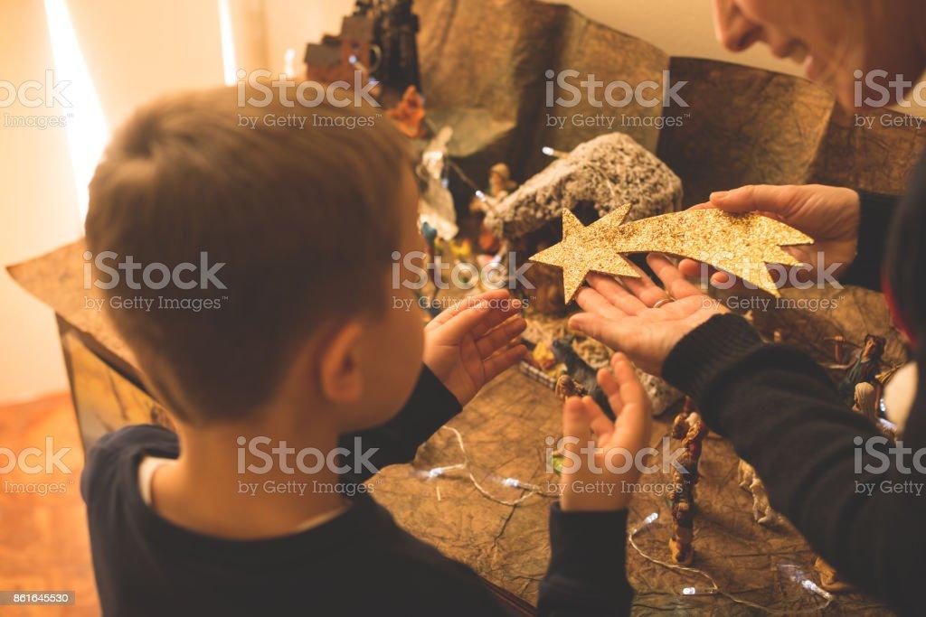Christmas - Mother and son making crib stock photo