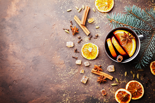 Christmas mulled wine or gluhwein with spices and orange slices on rustic table top view. Copy space for recipe.