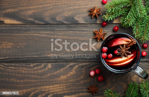 istock Christmas Mulled Wine with Apple and Cranberries. Holiday Concept Decorated with Fir Branches, Cranberries and Spices. 869637822