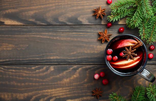 kerst glühwein met appel en cranberries. concept vakantie versierd met fir takken, veenbessen en specerijen. - gluhwein stockfoto's en -beelden