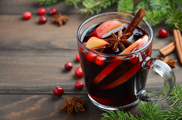 christmas mulled wine with apple and cranberries. holiday concept decorated with fir branches, cranberries and spices. - mulled wine stock photos and pictures