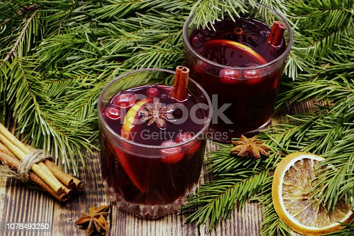 Christmas mulled wine with cranberries in glasses Winter warming drink with spices decorated with fir branches cinnamon dried oranges
