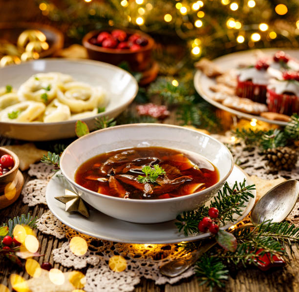 Christmas mushroom soup, a traditional vegetarian  mushroom soup made with dried forest mushrooms in a ceramik plate on a festive table. Christmas mushroom soup, a traditional vegetarian  mushroom soup made with dried forest mushrooms in a ceramik plate on a festive table. Polish Christmas dinner polish culture stock pictures, royalty-free photos & images