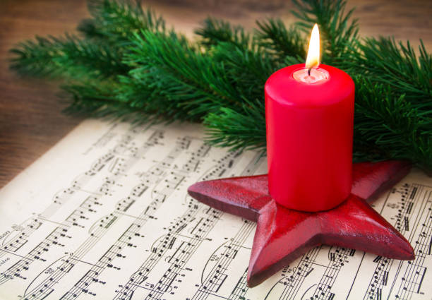 Christmas Music Sheet Music with Burning Candle stock photo