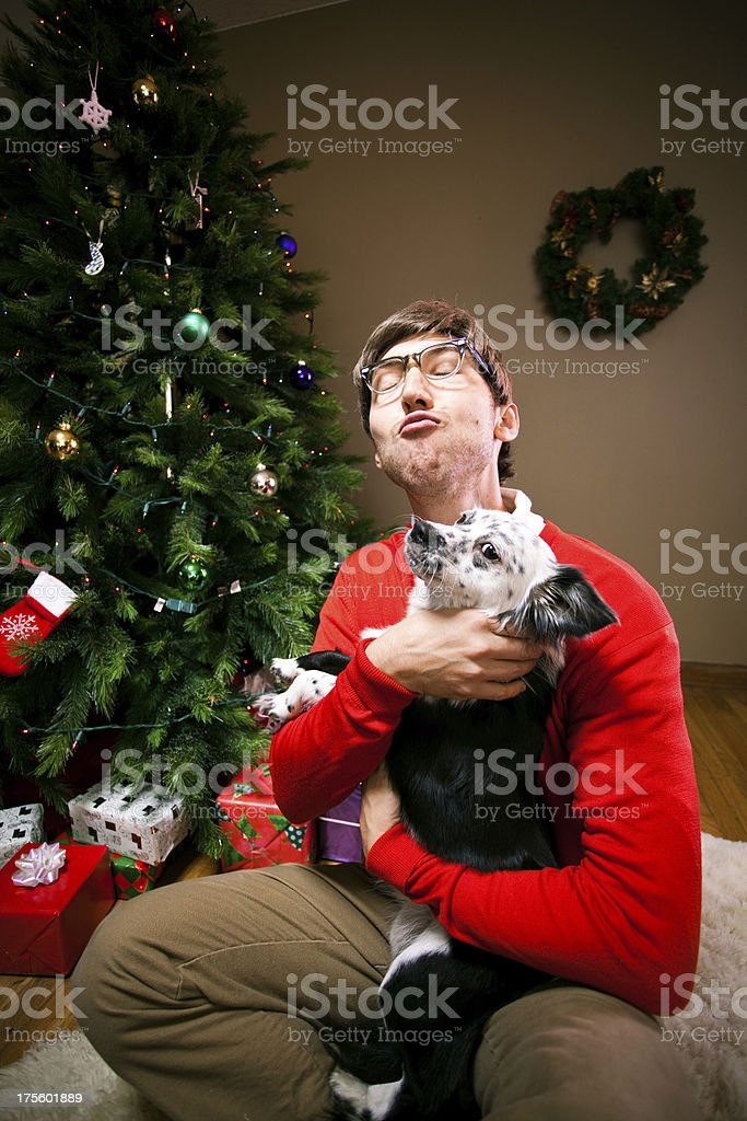 A goofy Christmas nerd man holding and kissing his puppy dog...