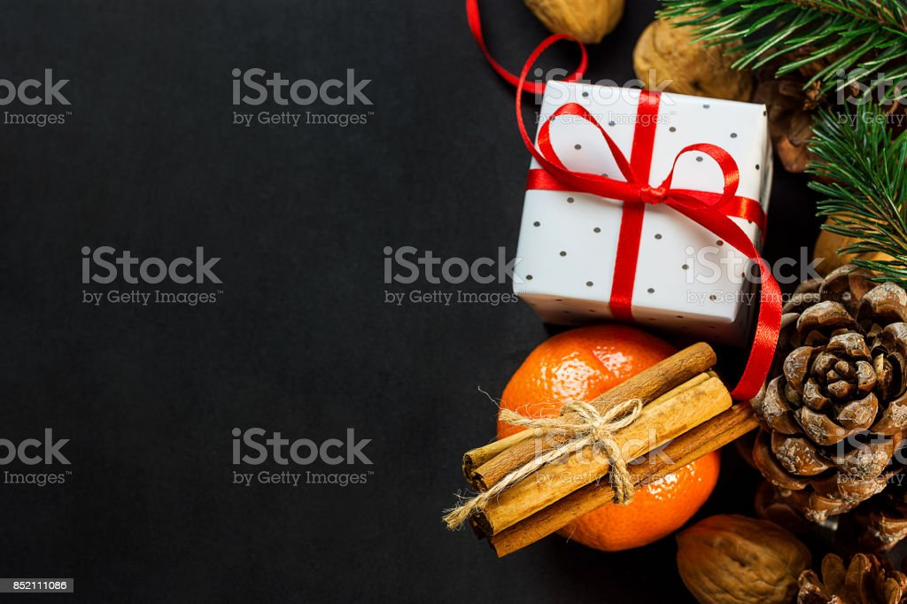 Christmas New Year Composition Greeting Card. Tangerine Cinnamon Sticks Pine Cones Fir Tree branches Gift Box with Curled Red Ribbon Nuts on Dark Background. Template Copy Space. stock photo