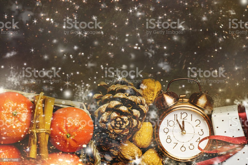 Christmas New Year Greeting Card Tangerines in Wicker Basket Vintage Alarm Clock Five Minutes to Midnight Pine Cones Gift Box Walnuts. Dark Background Snow Flakes Golden Glitter Magical. Copy Space stock photo