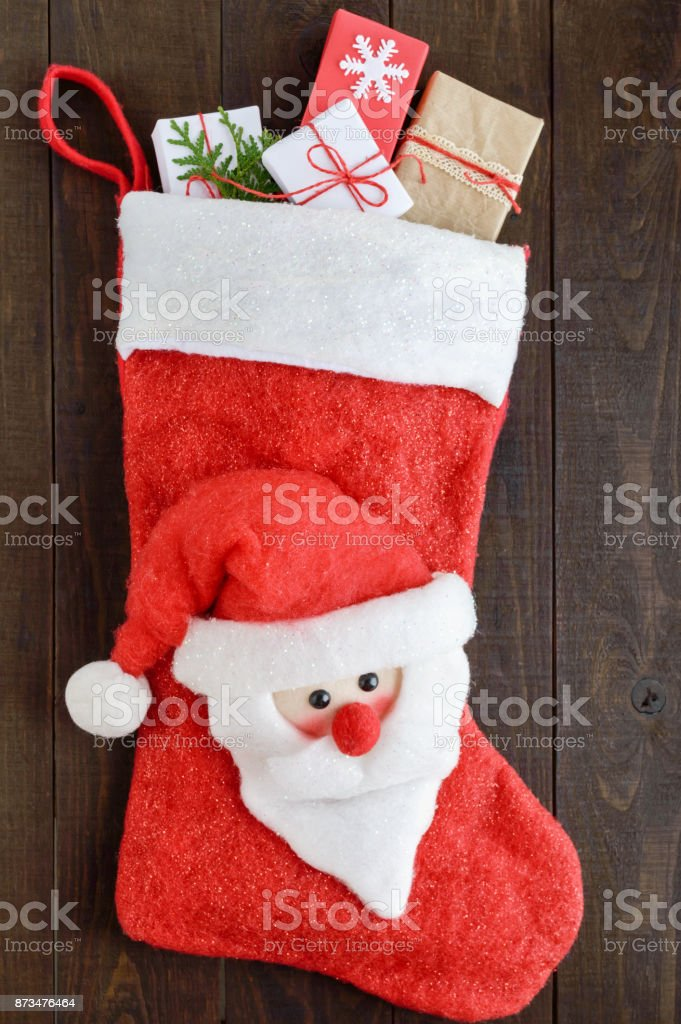 Christmas, New Year's boot for gifts with a Santa face, full of gift boxes on a dark wooden background. Theme of winter holidays. stock photo