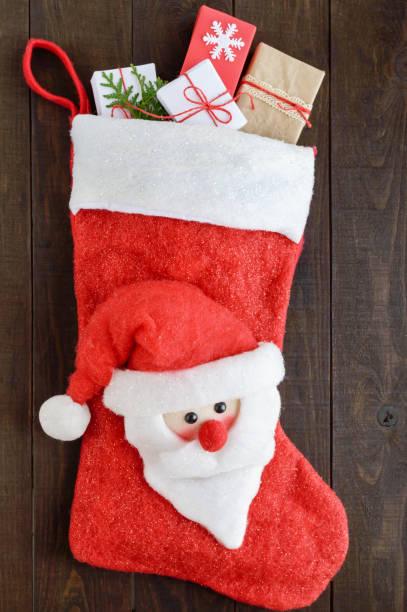 weihnachten, silvester boot für geschenke mit einem santa gesicht, voll von geschenk-boxen auf einem dunklen hintergrund aus holz. thema der winterferien. - kinder winterstiefel stock-fotos und bilder