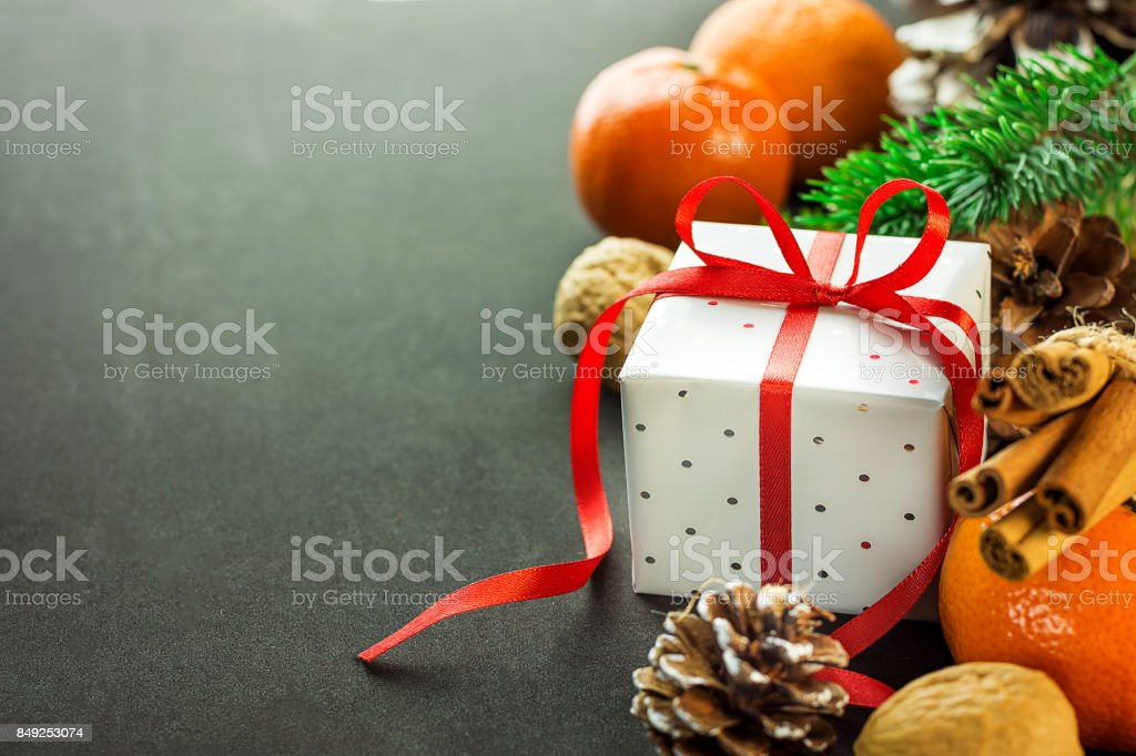 Christmas New Years gift box with red ribbon bow. Tangerines pine cones walnuts fir tree branches. Greeting card template dark background copy space. stock photo