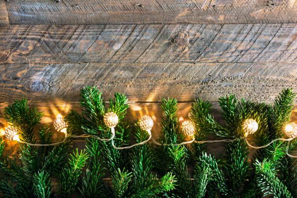Weihnachten Neujahr Grußkarte Poster Tannenbaum Zweige golden funkelnde Girlande Lichter auf rustikalen Holz Hintergrund Urlaub magische Atmosphäre. Hochauflösende Vorlage für Banner-Streamer – Foto