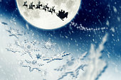 Huge Moon, Snowflakes and Santa Claus Sleight Silhouette Flying to Bring Presents