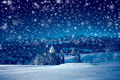 Beautiful Christmas night with snowfall. Christmas holiday landscape of mountains at starry night with blue sky