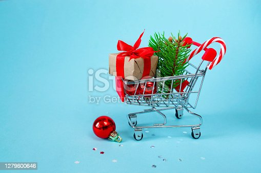 christmas online shopping concept. Shopping cart with gifts, Christmas decor, Christmas tree on a blue background. background. 3d illustration. Copy space, banner