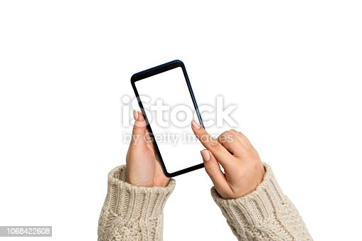 936543982 istock photo Christmas online shopping. female hands in sweater Touch screen mobile phone. Woman typing on mobile phone isolated on white background 1068422608