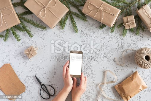 istock Christmas online shopping, top view concept. Woman buys presents for Xmas eve with smartphone with copy space. Winter holidays sales 1060431670