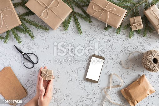 istock Christmas online shopping, top view concept. Woman buys presents for Xmas eve with smartphone with copy space. Winter holidays sales 1060447636