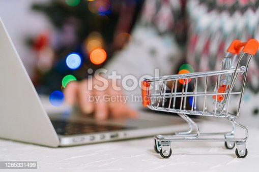 Christmas online shopping. Woman buy presents, prepare to xmas, among shopping cart and presents box. Winter holidays Merry Xmas winter holidays sales concept