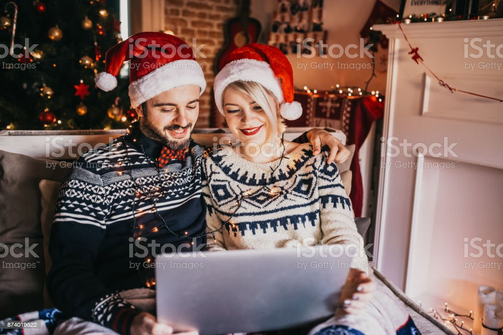Christmas Online Shopping. Young couple with laptop buying online. Christmas and New Year Gifts. e-shopping stock photo