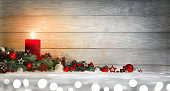 Christmas or Advent wood background with a burning candle on snow, decorated with fir branches, lights and ornaments, panoramic format with copy space