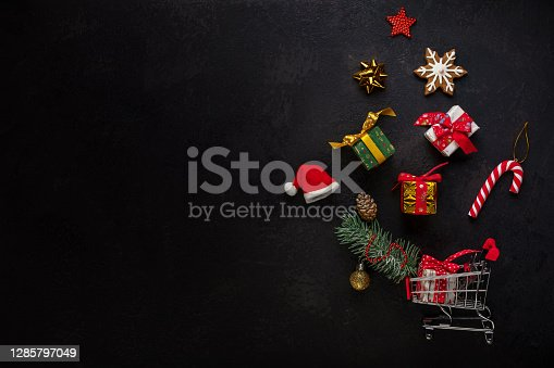 Christmas or Boxing Day background concept. Top view of shopping cart and levitating Christmas decorations with gift boxes, gingerbread cookie snowflake, candy cane, Christmas ornament and cone on branch of fir tree on black background.