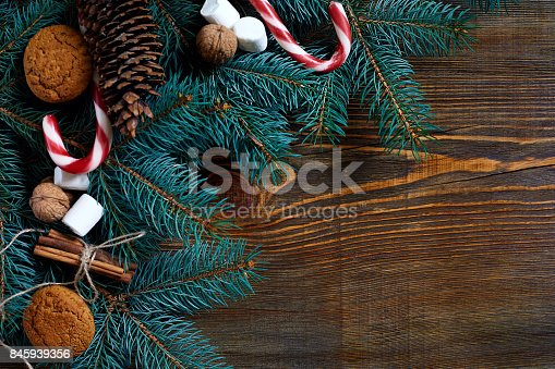 istock Christmas or New Year background with cookies, spices, cinnamon, nuts and fir tree branch on dark wooden background 845939356