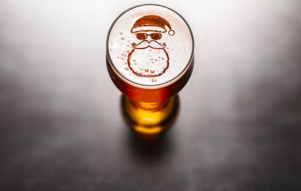 Christmas or New Year beer Christmas or New Year beer concept. Star symbol on beer glass foam on black table, view from above lager stock pictures, royalty-free photos & images