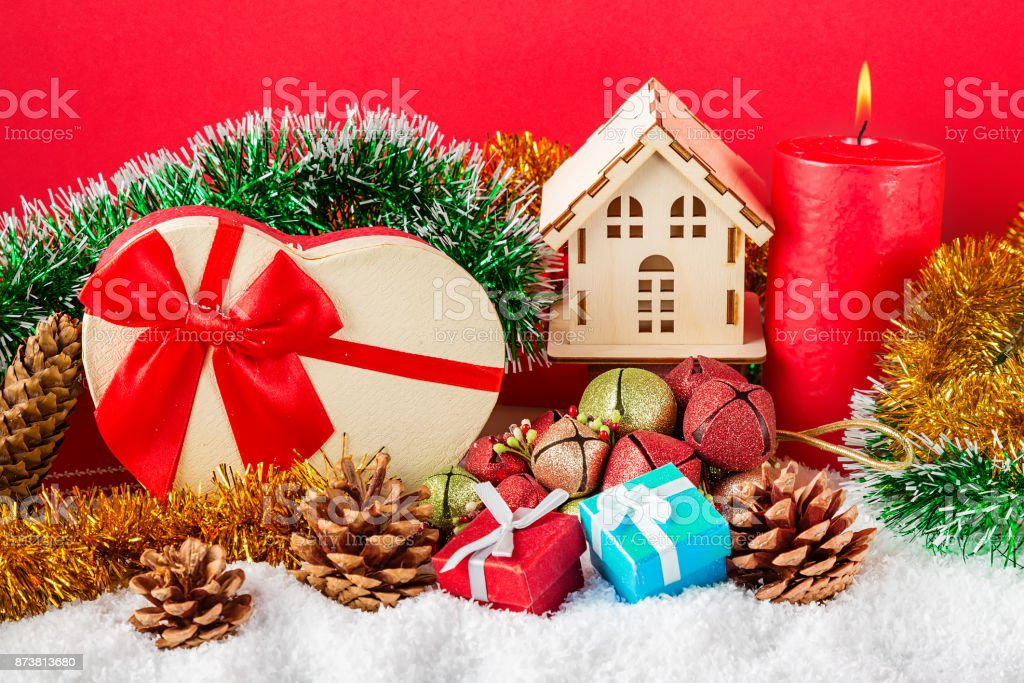 Christmas or New Year card. Burning red candle, cones, giftboxes, decorative house, toys and spangle against red background. stock photo