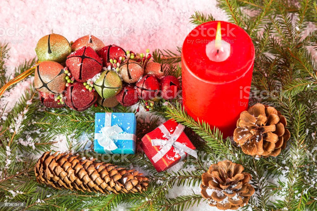 Christmas or New Year card. Burning red candle, cones, giftboxes, toys on fir tree branches and snow. Close up image stock photo
