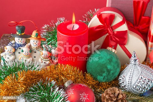 istock Christmas or New Year card. Funny snowman family with burning red candle, cone, giftboxes, balls and spangle against red background. 863655574