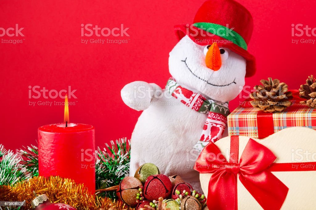 Christmas or New Year card. Funny snowman with burning candle, cones, giftbox anf spangle against red background. stock photo