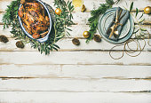 Christmas or New Year celebration table setting. Flat-lay of roast chicken or turkey, plates, silverware and toy holiday decoration over white wooden background, top view, copy space